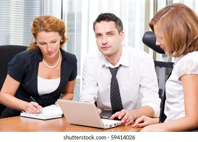 Professional business manager using his laptop computer while his red-haired colleague writing something in her notebook in Hi Res.