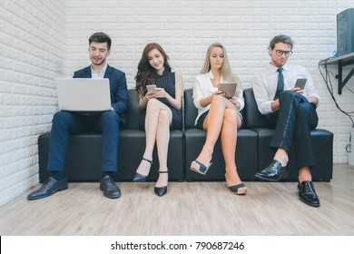 Professional business people sitting on the sofa using laptop and smartphone device for work in the office, business concept