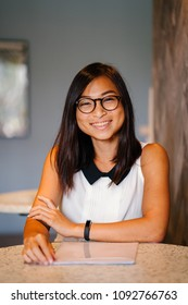 Professional business portrait of an attractive, young Chinese Asian woman. She and is wearing nerdy spectacles and is smiling for her head shot.