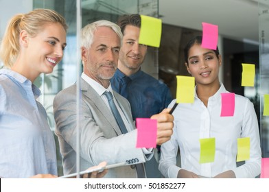 Professional business team discussing ideas on sticky notes. Businessman showing written work on sticky notes. Creative team discussing over adhesive notes.