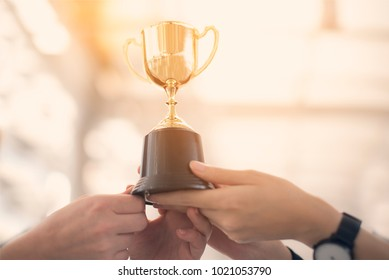 Professional business teamwork holding trophy cup celebrating with trophy award for successful in business ,achievement and businessman concept.