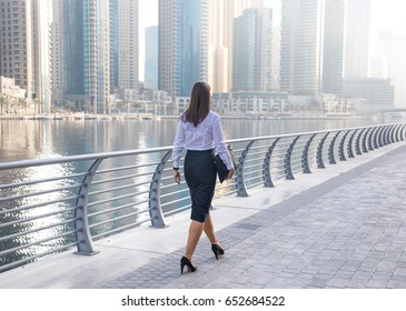 Professional business woman in office attire walking on a boardwalk.
