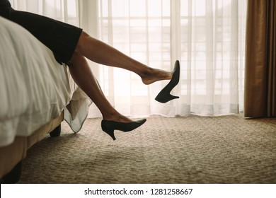 Professional business woman relaxing on hotel room bed after travelling for work. Female being tired after a long journey resting on bed.