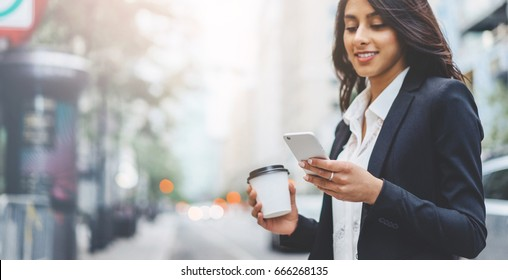 Professional business woman using technology outside, Professional female manager reading information in internet while walking outdoor