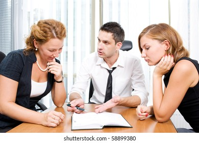 Professional business workers discussing serious business projects with their boss who is showing them something in his notebook in board room.