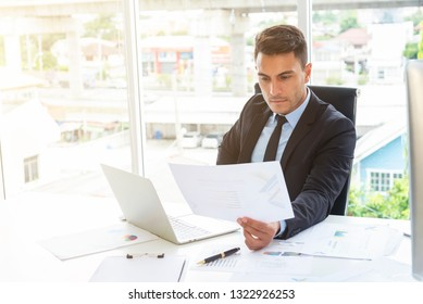 Professional businessman reading project reported in office. Portrait of smart business people working in office concept.