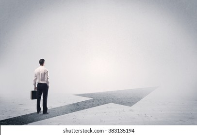 A professional businessman thinking while standing on a black arrow pointing forward in grey space concept