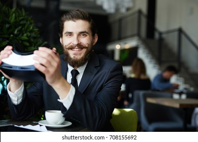 Professional businessman with vr headset in hands enjoying leisure in cafe