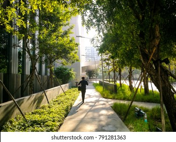 Professional businessman walking near small garden and big modern office in the morning with rays sunlight. working life in the city with green environment.