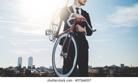 Professional businessman wearing black suit and standing with modern orange bicycle, panoramic view of the city in the background, flare light, outdoors