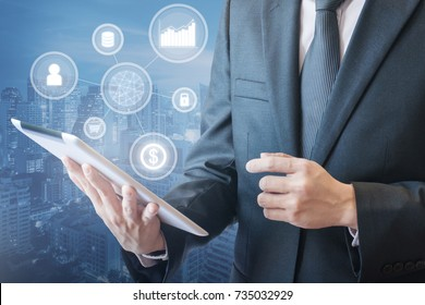 Professional businessman is working his business on tablet via wireless network connection in finance and banking technology concept with cityscape in blue tone background