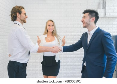 Professional businessmen shaking hands and smiling after discuss new project success, supported by colleagues applauded in the office, business people concept