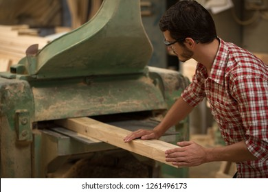 Professional and busy joiner working with wood and carpenter's gauge in joiner's shop. Confident woodworker in checked shirt standing, holding timber and machining it.