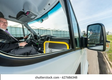 Professional cab driver looking away while driving taxi on road