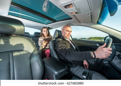 Professional cab driver riding taxi while female passenger using digital tablet