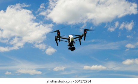 Professional Camera Drone flying in clear blue Sky partly clouded