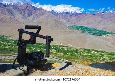 Professional camera on tripod shooting beautiful landscape view of Himalayas, background with blue sky, white clouds and Himalaya mountains in Ladakh, region in Jammu and Kashmir,India.