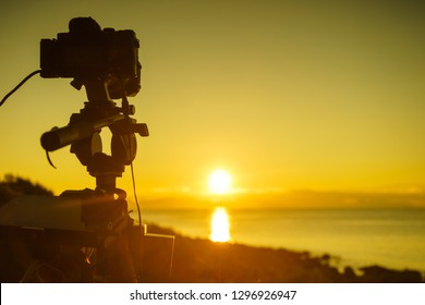 Professional camera taking picture film video of sunrise over sea surface, Greece Peloponnese.
