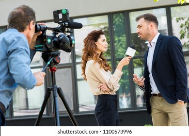 professional cameraman and journalist interviewing businessman near office building