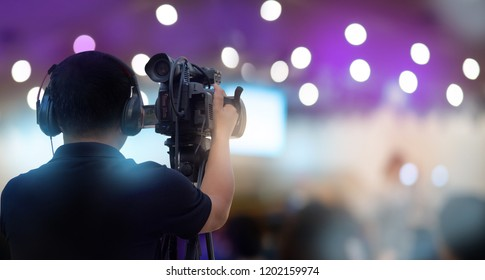 professional cameraman on stage to record event with camera equipment for entertainment and media