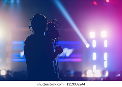 professional cameraman record live concert with beam spot and light performance