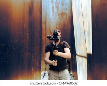 professional cameraman, recording a video footage using a professional dslr camera and gimbal. Blogger, vlogger, storyteller, traveler concept
