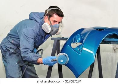 Professional car body repair, Painting blue bumper.