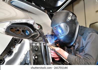 Professional car body repair, welding panels.