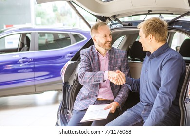 Professional car dealer and his male customer sitting in an open trunk of an auto at the dealership salon shaking hands buying selling vehicle automobile transportation agreement sales.