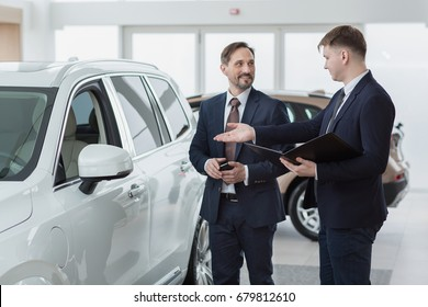 Professional car dealer showing a new car to his client. Mature businessman choosing a vehicle to buy communication occupation job service customer consumer retail retailer sales offering discount