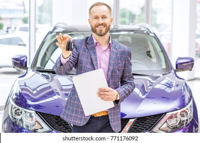 Professional car dealer smiling joyfully holding out car keys to the camera posing in front of a new automobile at the dealership salon profession occupation business salesperson seller retail rent.