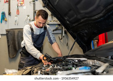 A professional car mechanic is changing an air filter, doing car service and maintenance of the vehicle. Oil and fuel filter changing. Service interval.