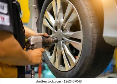 Professional car mechanic changing car wheel in auto repair service