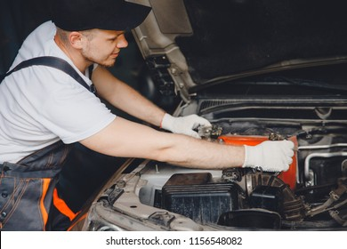 Professional car mechanic connected battery in auto repair service.
