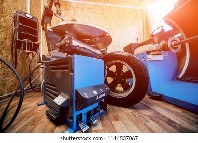 Professional car mechanic replace tire on wheel. Auto repair service.