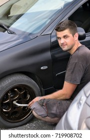 Professional car mechanic screws the wheel to the car