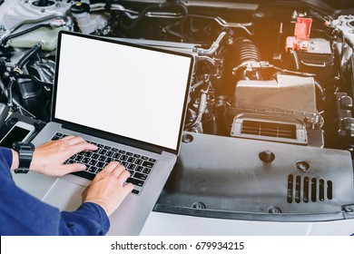 Professional car mechanic working in auto repair service using laptop bon car
