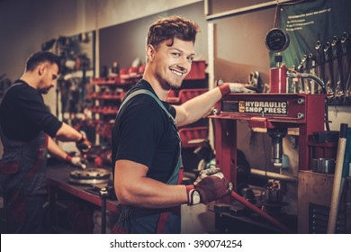 Professional car mechanic working with hydraulic press in auto repair service.