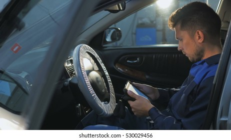 Professional car mechanic working in modern auto repair service and checking engine