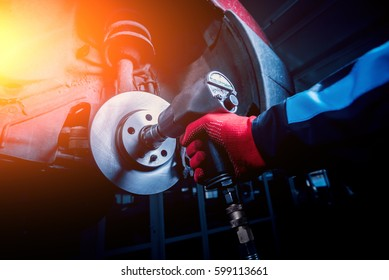 Professional car mechanic working with pneumatic wrench in auto repair service. Repair of wheels