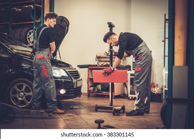 Professional car mechanics inspecting headlight lamp of automobile in auto repair service.