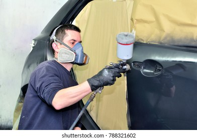 Professional car painter working at a black vehicle.