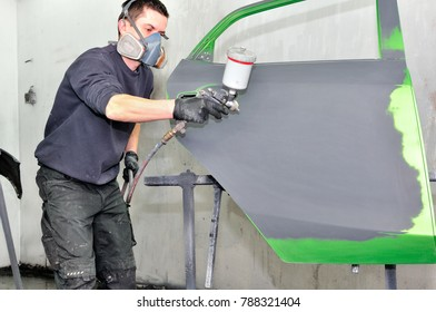Professional car painter working at a green door.