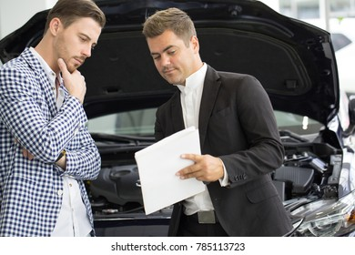 Professional car salesman showing papers to sign to his cutomer. Young handsome man preparing to sign documents while buying a new car safety insurance agreement consumerism vehicle.