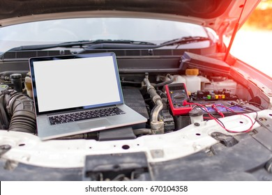 Professional Car Service use a laptop and multi-meter to repair ecu problems.