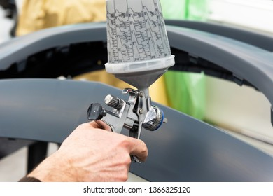 Professional car varnisher at work in a service station - Serie car repair workshop