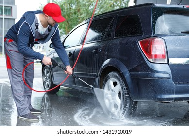 Professional car wash worker is washing client's car