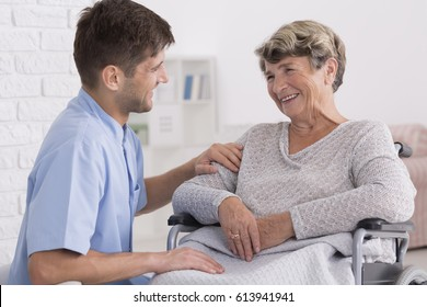 Professional caregiver comforting smiling elderly woman on wheelchair