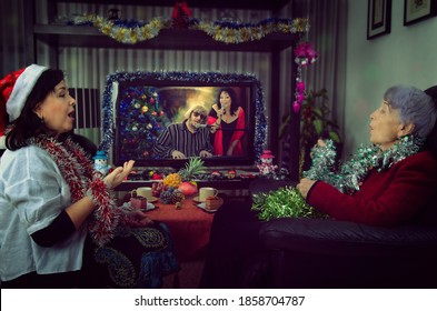 A professional caregiver and a senior adult woman sitting in front of a TV on Christmas Eve. They sing carols along with singers on the holiday channel. The room is decorated with tinsels.