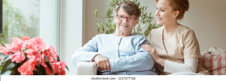 Professional caretaker with her senior charge sitting on a sofa in a bright living room of an assisted living house. Blooming flowers on a windowsill. Panorama.